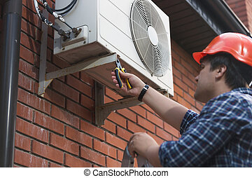 Technician in hardhat connecting outdoor air conditioning unit