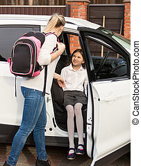 Mother helping daughter to get inside the car after school...