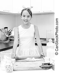Black and white portrait of cute girl rolling and kneading...