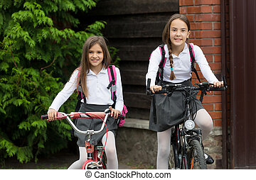 Two happy smiling girls in uniform riding to school on...