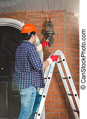 Young worker in hardhat repairing outdoor lamp at house