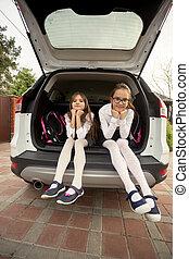 Two cute girls in school uniform sitting in open car trunk