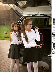 Two schoolgirls girls taking school bags out of car trunk