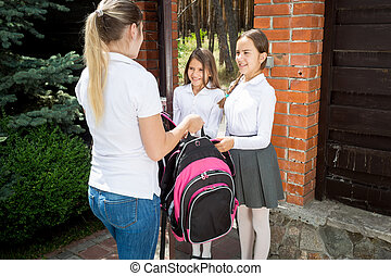 Young caring mother seeing off her daughter to school at...