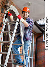 Young electrician in hardhat climbing the stepladder