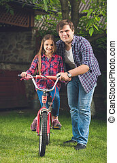 Young father teaching his daughter how to ride a bicycle