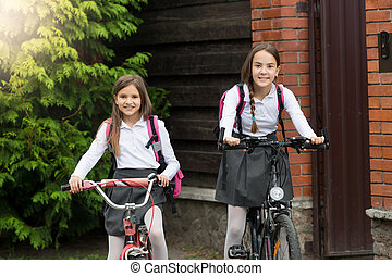 Two smiling girls leaving to school on bicycles