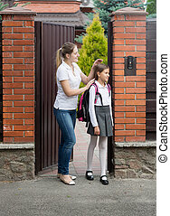 Cute 10 year old girl in uniform going to school from house