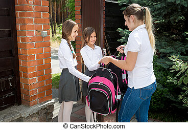 Beautiful young woman seeing off her daughters to school at...