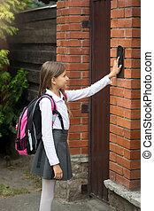 Schoolgirl with rucksack ringing in doorbell