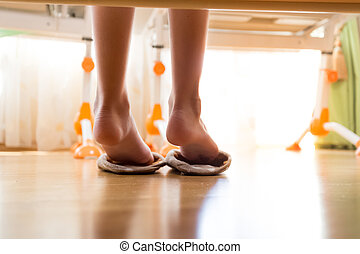 Photo from under the bed on female feet putting on slippers
