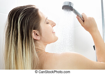 Portrait of young woman with long blonde hair washing in...