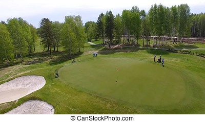 Aerial view of golfers playing on putting green. Professional players on a green golf course.