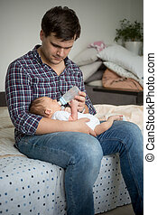 Young father sitting on bed and feeding his newborn son