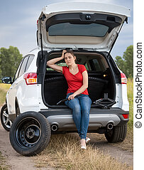 Upset woman sitting open car trunk and waiting for help to change tyre
