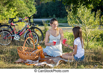 Woman having picnic by the river with 10 years old daughter....