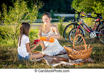 Smiling woman sitting on blanket under big tree with her...