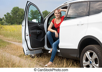 Beautiful smiling female driver relaxing in car at the field