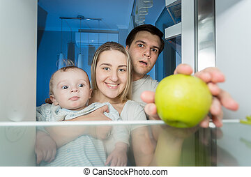 View from inside the refrigerator on smiling family looking for something to eat