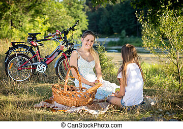 10 year old girl having picnic by the river with young...
