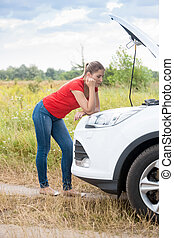 Young sad woman looking at broken car and waiting for help