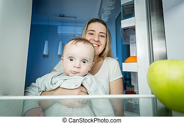 Mother holding baby and taking green apple from apple. View from inside of refrigerator