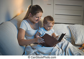 Young mother storytelling to her adorable baby boy at bed