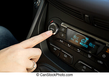 Closeup of woman adjusting temperature on car climate control system