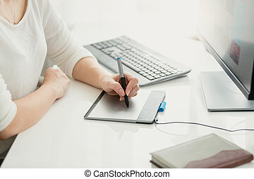Closeup of young woman using graphic tablet at office