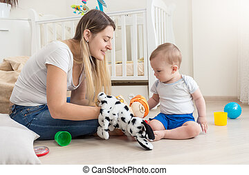 Smiling mother wearing dog puppet on hand and playing with...
