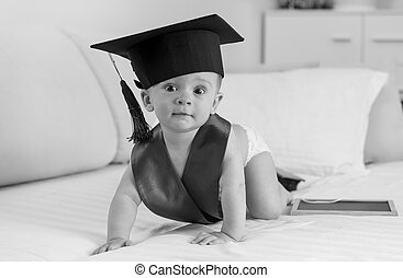 Black and white image of adorable 10 months old baby boy in graduation cap crawling on bed