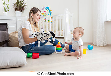 Young mother making puppet show with her adorable baby boy