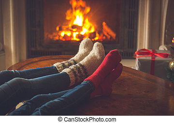 Family in cosy knitted socks warming at fireplace decorated...