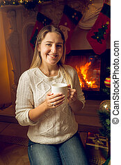 Portrait of beautiful young woman drinking tea at the fireplace