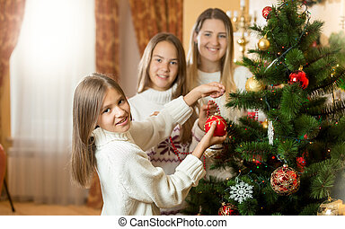 Happy smiling family decorating Christmas tree at living room