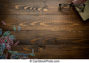 Wooden background with notebook and colorful paperclips....