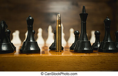 Big riffle bullet among chess pieces. Concept of weapon...