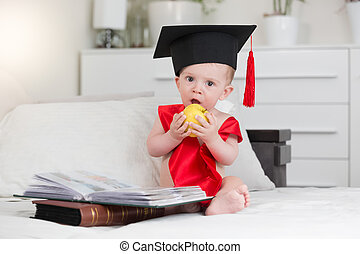 Portrait of adorable baby boy in graduation cap sitting in from of books and biting apple
