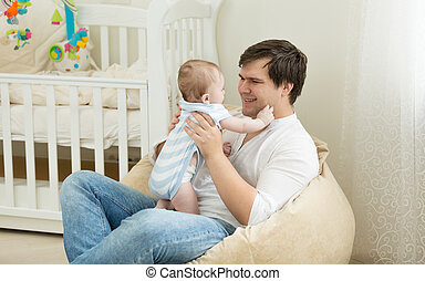 Happy young man playing with his baby at bedroom