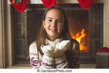 Portrait of cute teenage girl sitting at fireplace and blowing snow from hands