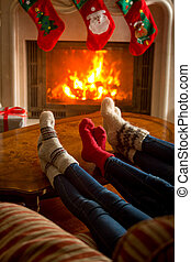 Family wearing knitted socks sitting by burning fireplace