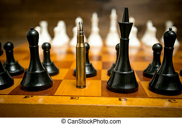 Big riffle bullet in row of black chess pieces. Concept of...