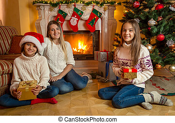 Cute girls with young mother sitting at fireplace in living room decorated for Christmas