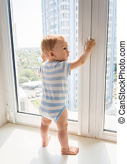 Little baby boy standing on window sill and pulling window handle