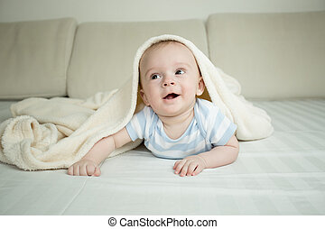 Happy little baby crawling on bed under blanket