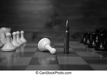 Black and white photo of riffle bullet on chessboard....