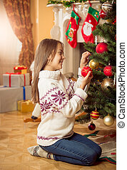 Beautiful girl in sweater sitting on floor at living room and decorating Christmas tree