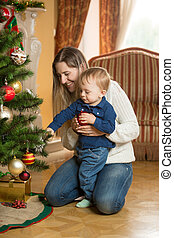 Mother showing her baby son how to decorate Christmas tree with baubles