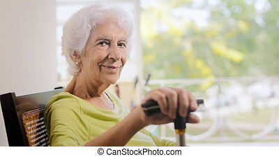 Portrait Old Lady Sitting On Rocking Chair Holding Stick