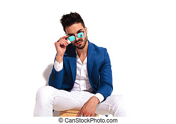 fashion male model sitting and holding his sunglasses